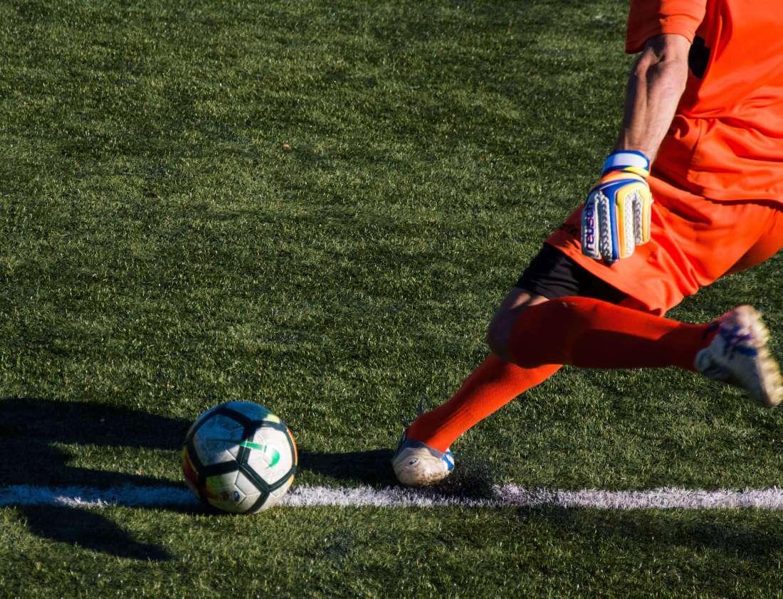 Football player kicks the ball - a stock image from Unsplash