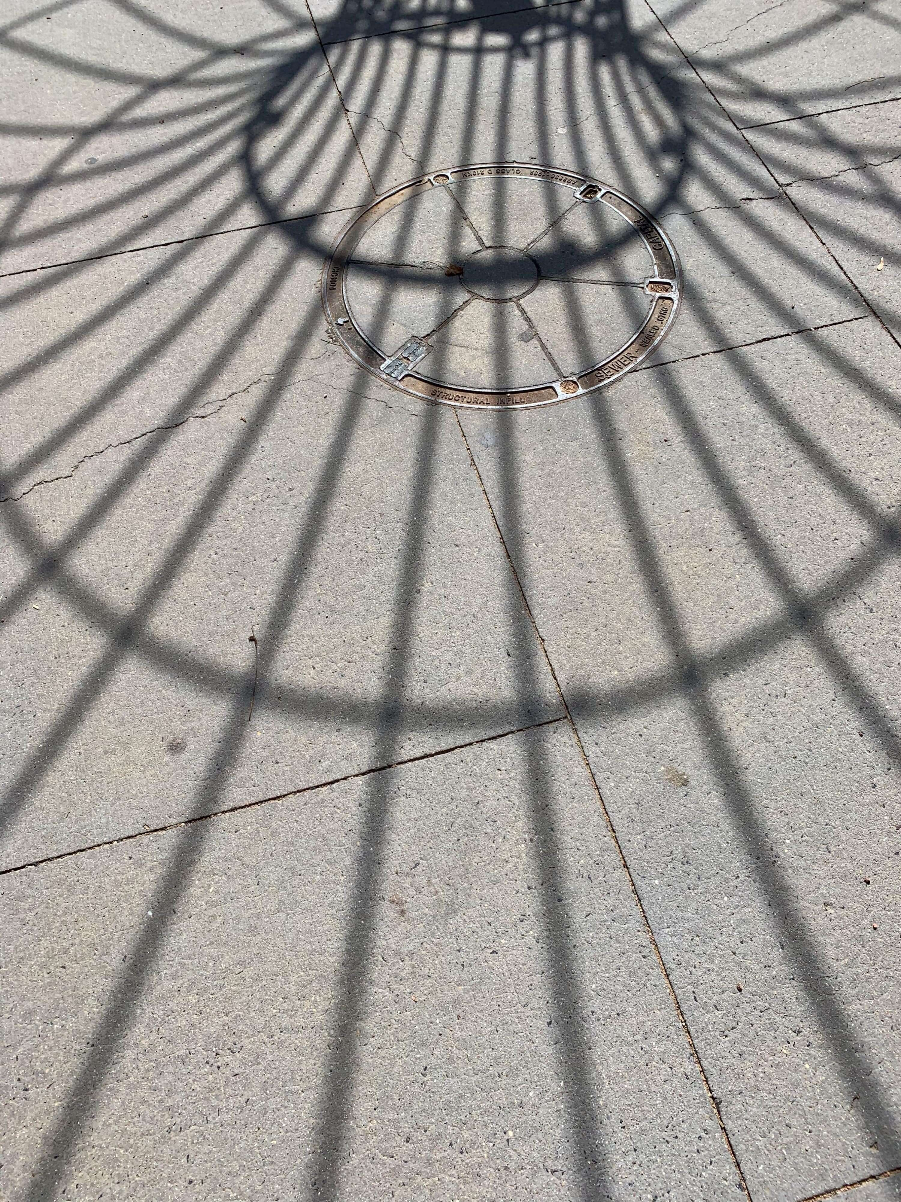 shadow of a circular city structure on the ground - with a circle in the middle and lines extending through it