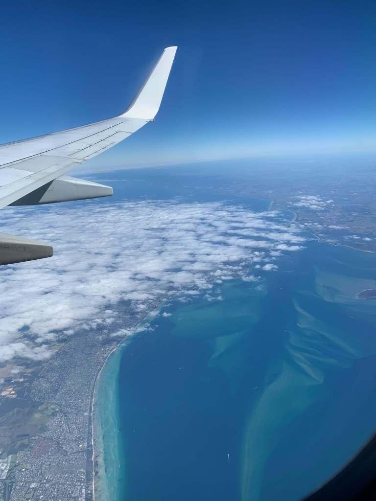 photo of the ocean as seen throug the flight windor