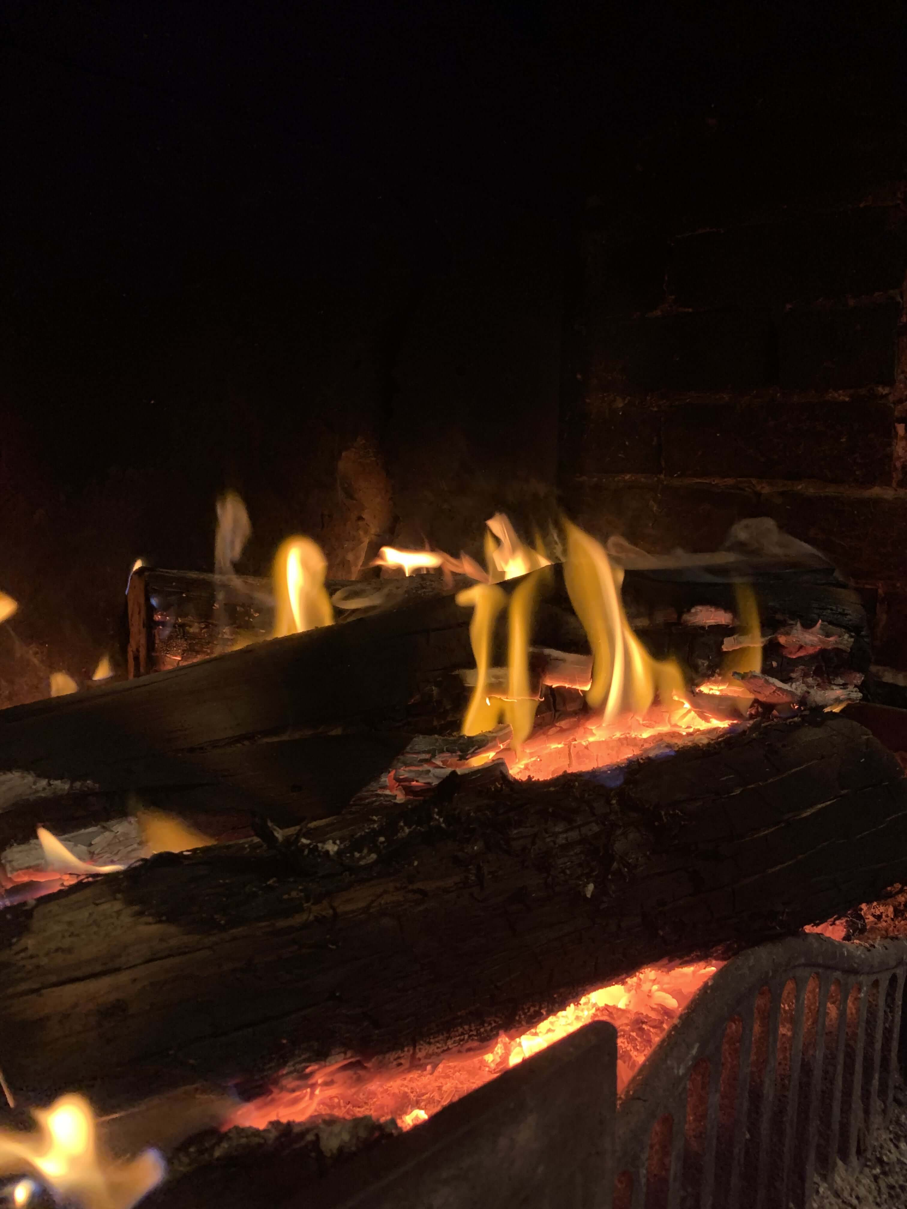 photo of black logs burning in a fireplace