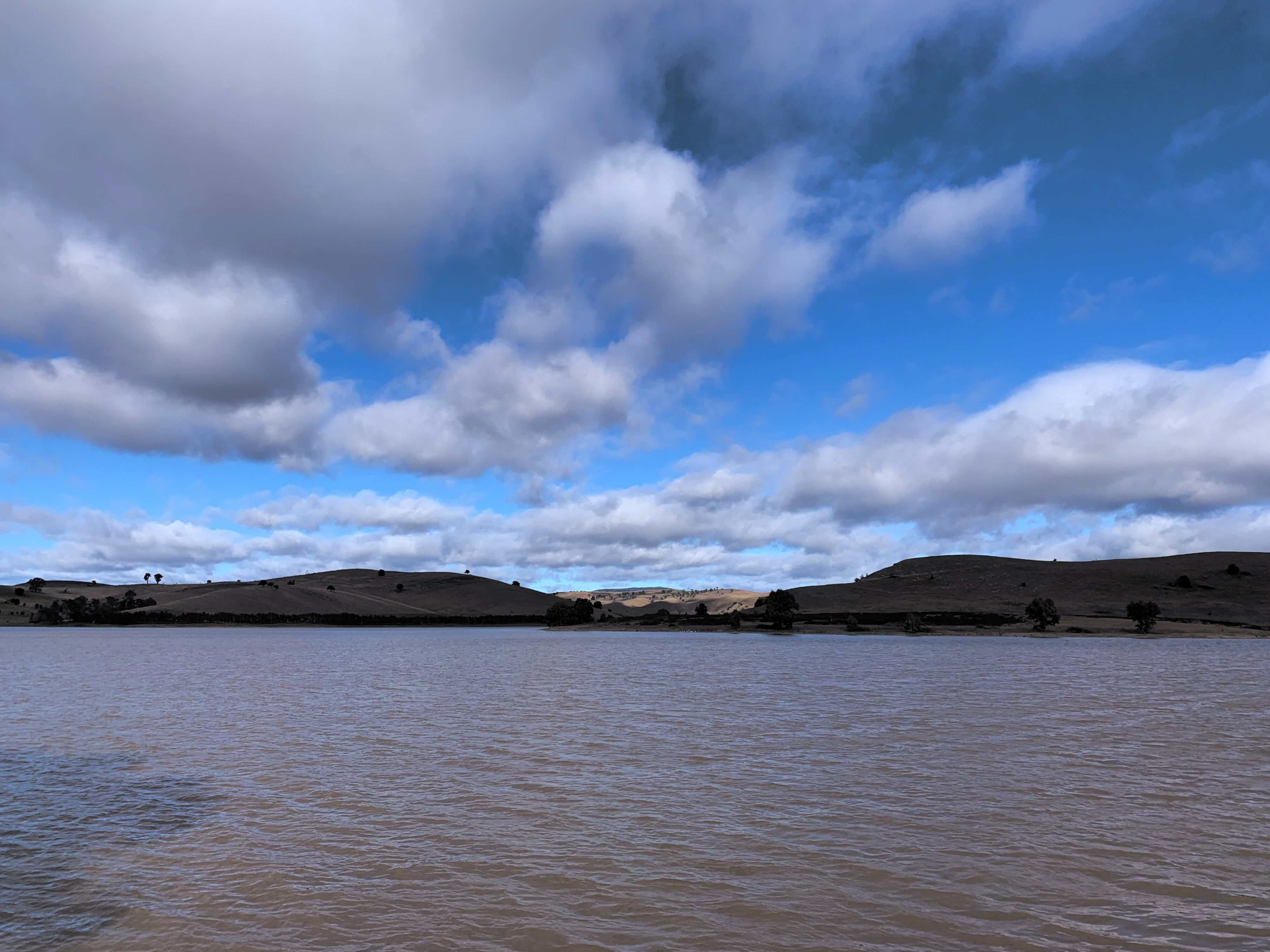 photo of a quiet lake in the mid afrernoon on a partly cloudy day