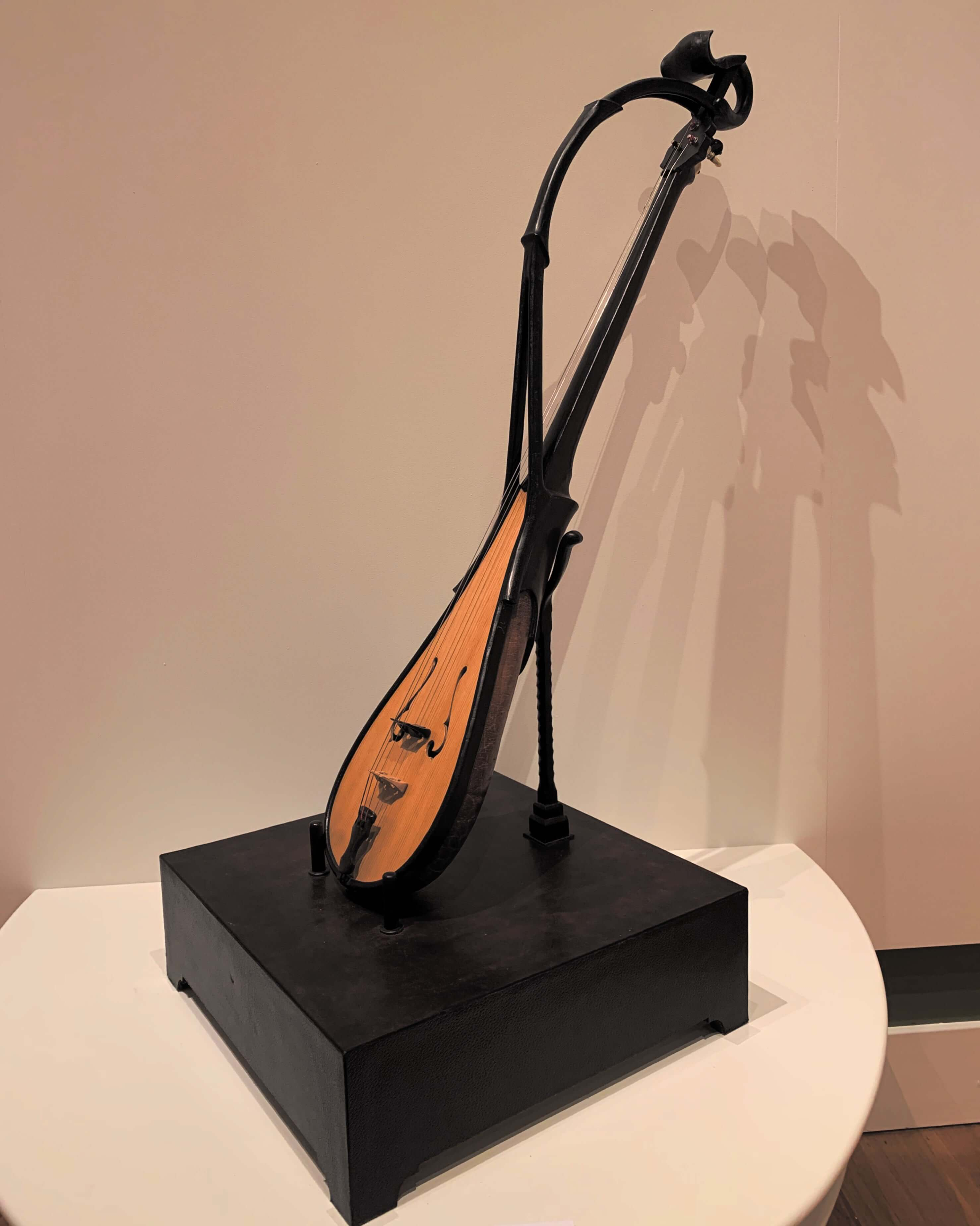 A string musical instument made of leather on display at the Queen Victoria Museum and Gallery in Launceston, Tasmania - the instument's shadows are visible on the wall behind it