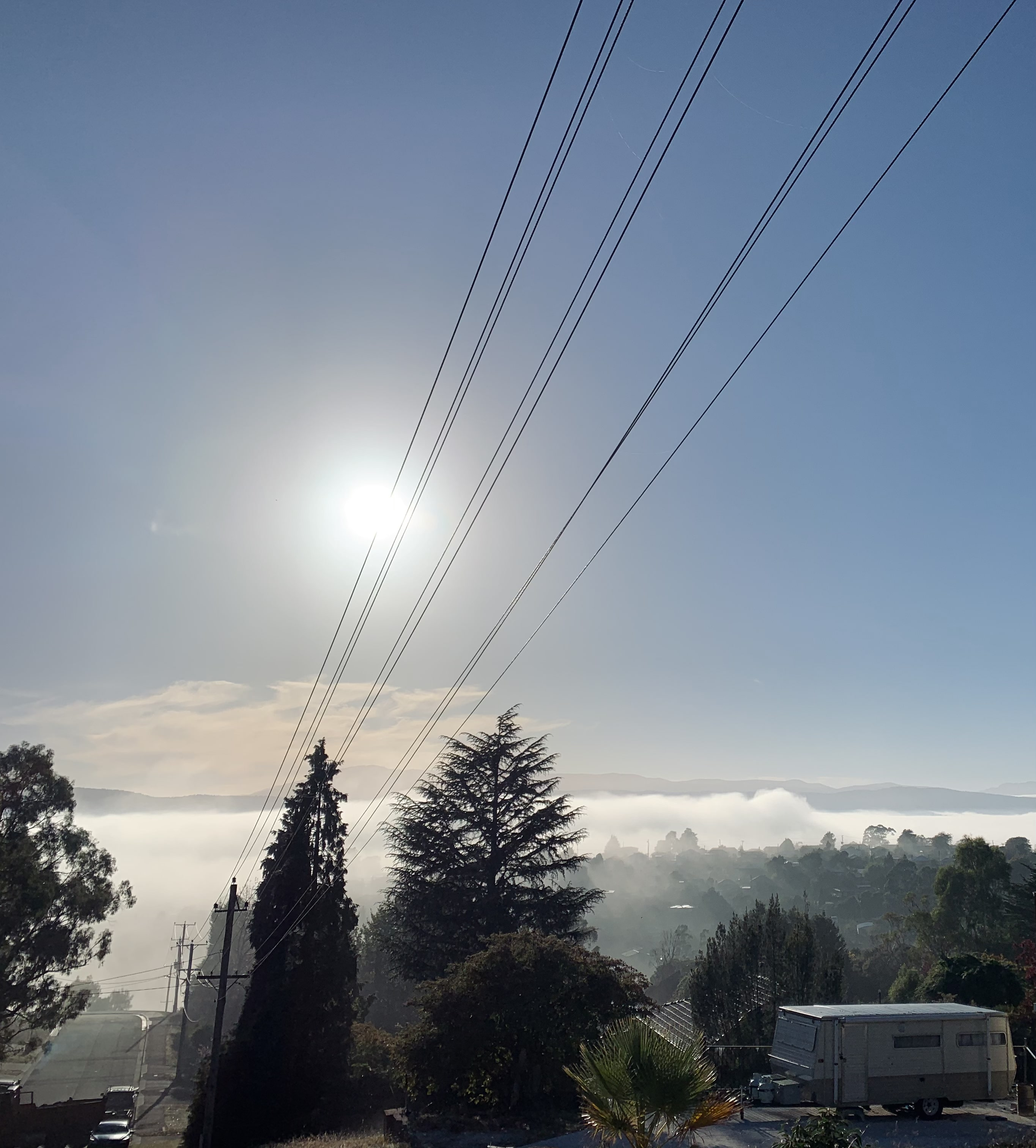 morning fog over the Launceston as seen in the distance with the sun lightly visible