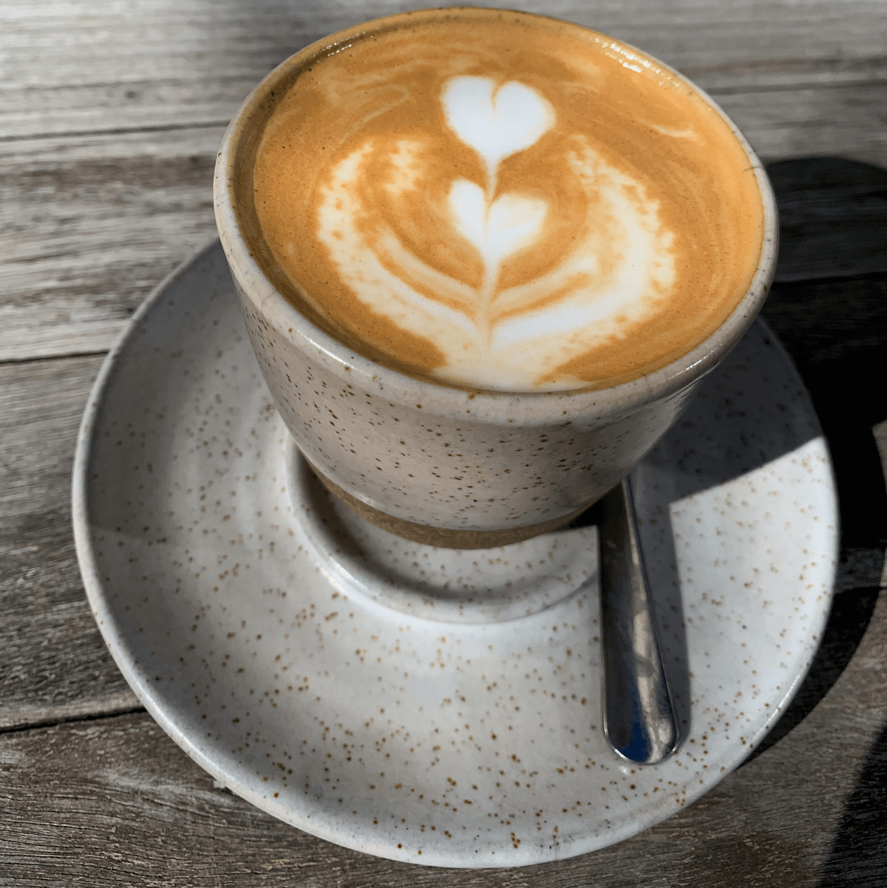 closeup photo of a coffee with latte art in a clay cup