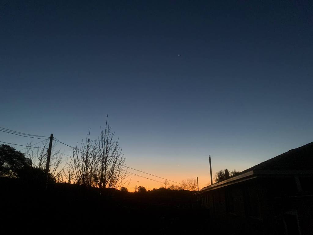photo of the sunset in the horizon, with darkness in the surrounds