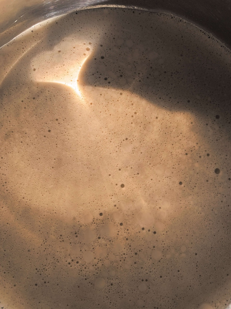 Close up photo of coffee in a pot witg the aunlight reflecting on it. The light has formed the shape of a heart.